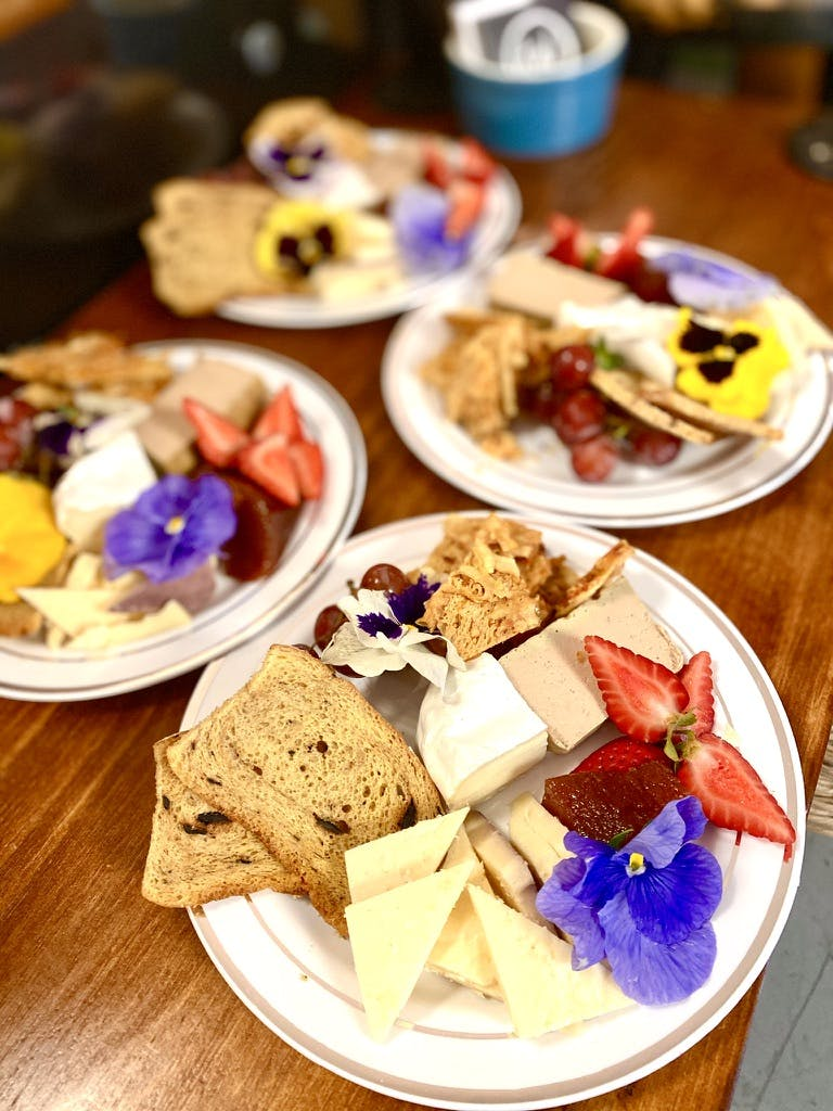 a wooden table topped with plates of food on a plate