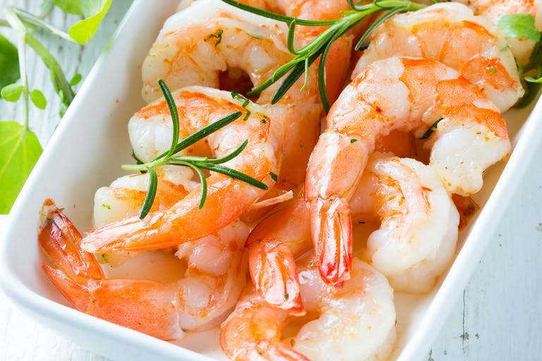a close up of a plate of shrimp and vegetables