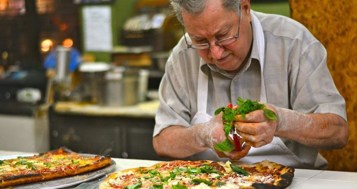 a man holding a slice of pizza