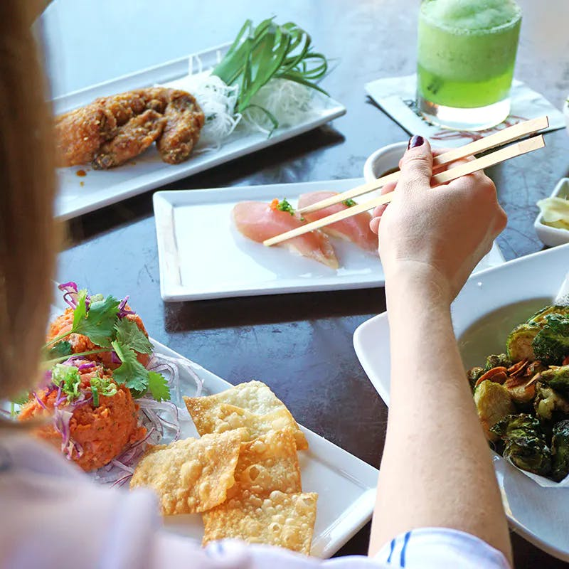 a woman sitting at a table with a plate of food