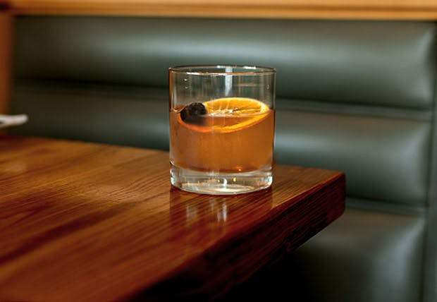 a glass of orange juice on a wooden table