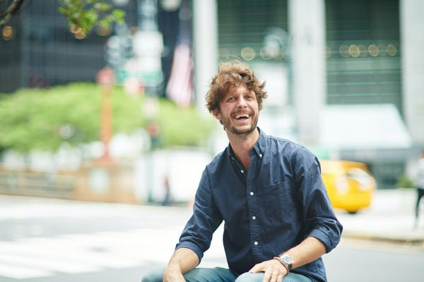 a man sitting on a sidewalk