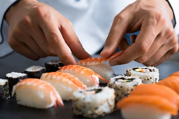 a close up of a person cutting a piece of sushi