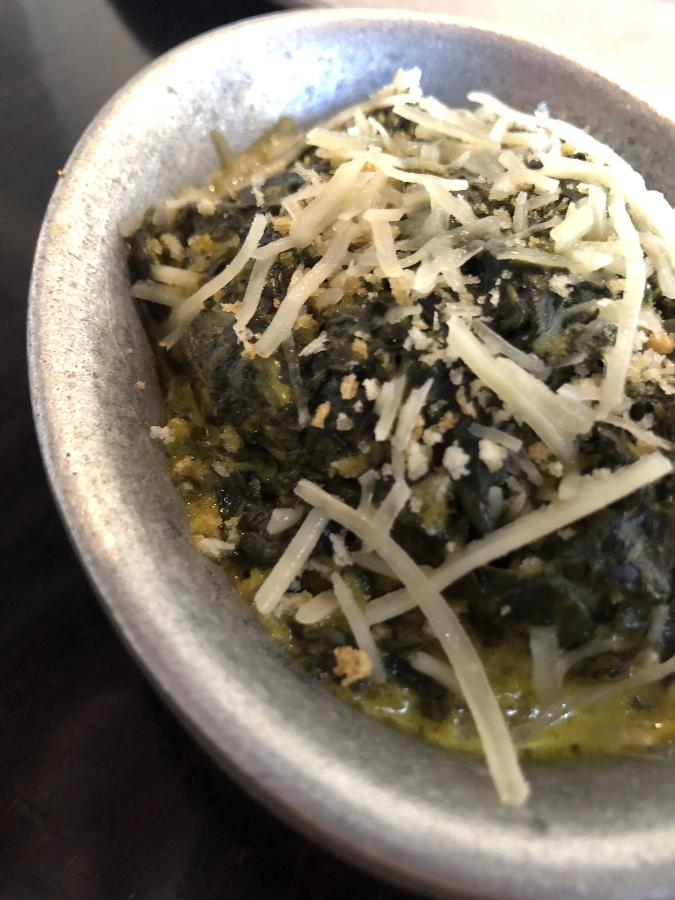 a bowl topped with spinach and chesse