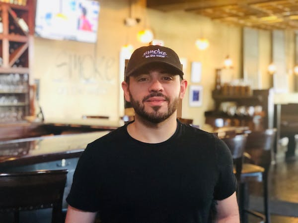 a man standing in front of a restaurant