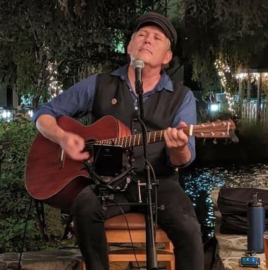 a man standing next to a guitar