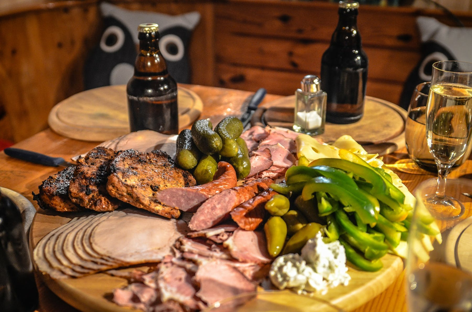 a plate of different types of meat, green pepper, cheese, jalapeño and pickles on a table