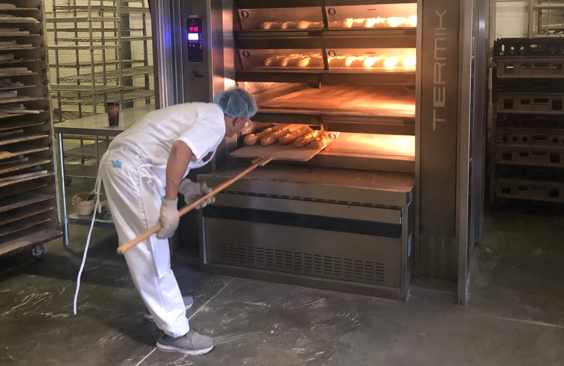 a man putting bread in an oven