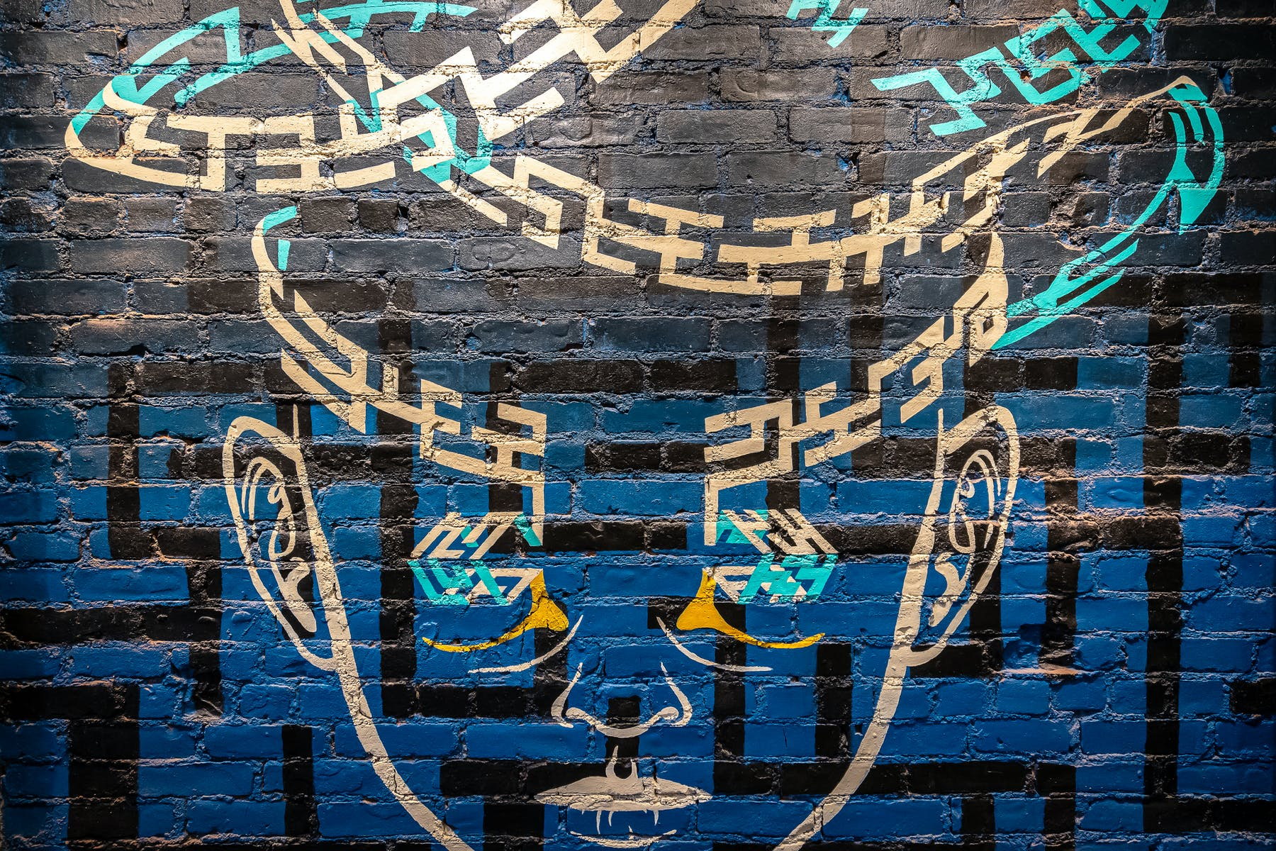A brick wall painted blue and a gold face