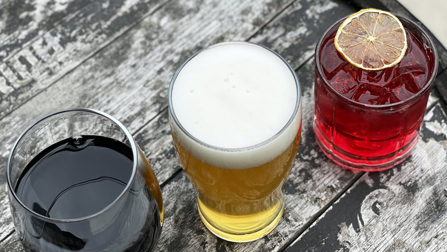 a glass of red wine, glass of beer, and a red cocktail on barrel