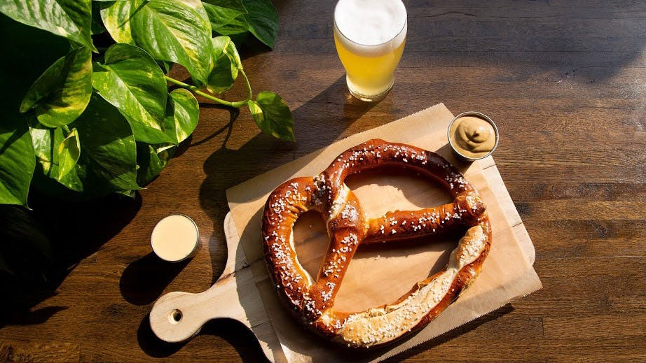 a pretzel sitting on top of a wooden board with mustard sauce on the side and beer glass with a plant in the corner