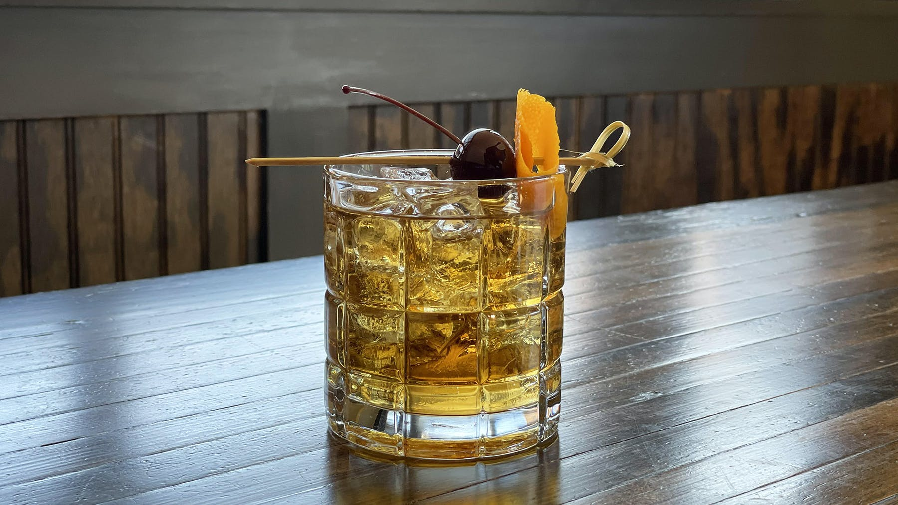 a glass of our Rivercrest Old Fashioned sitting on top of a wooden table
