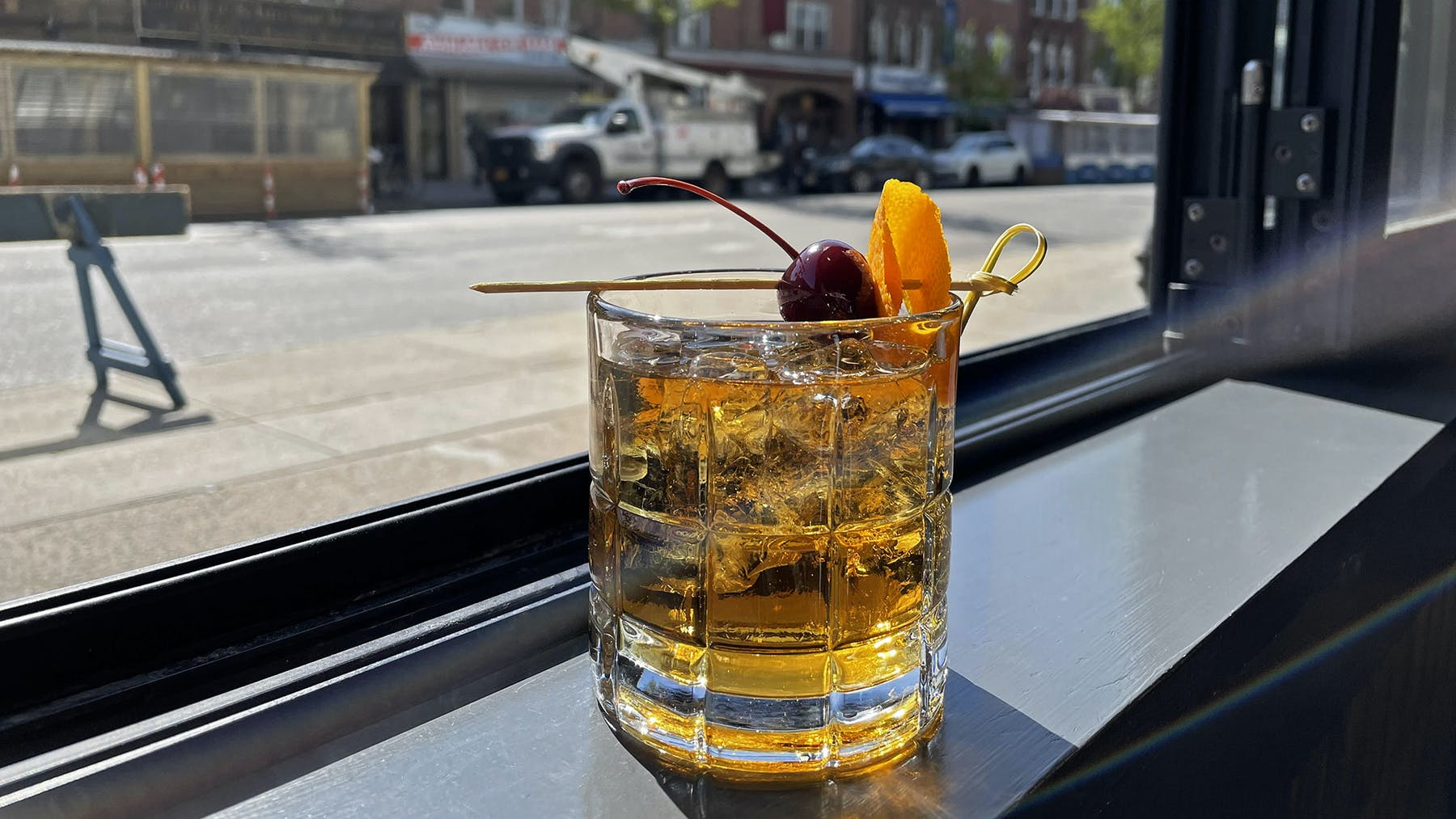 a glass of our Rivercrest Old Fashioned on a window ledge