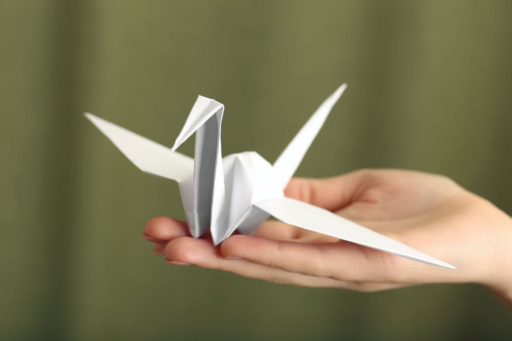 a hand holding an origami crane