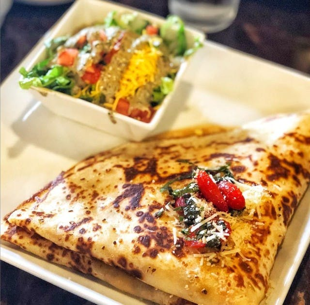 a crepe sitting on a plate with a side salad