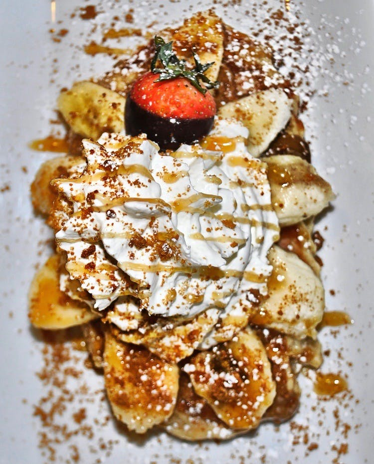 a waffle with peanut butter, banana, whipped cream, and caramel, on a plate on a plate