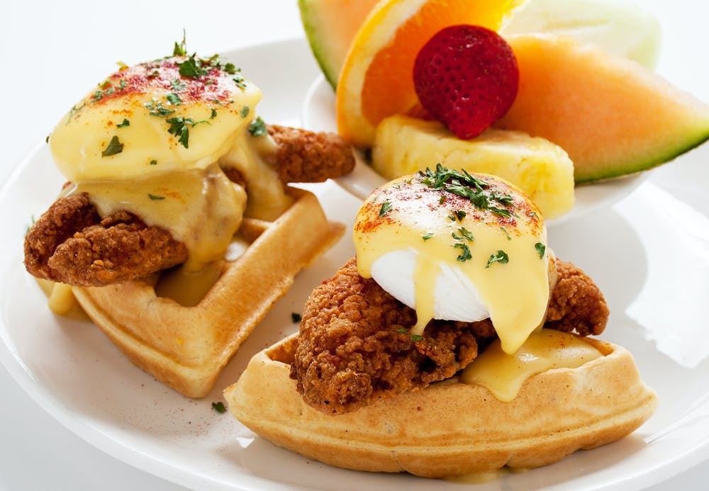 Omelets & Benedicts title. photo of bowl of assorted fruit and eggs benedicts on waffles