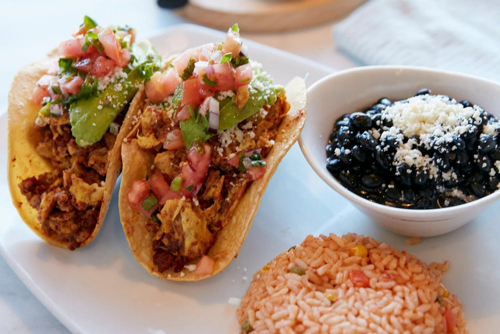 South of the border title. photo of two tacos, black beans and spanish rice