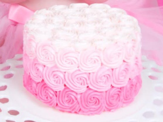 a pink and white cake on a plate
