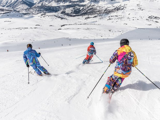 a group of people skiing down a snow covered slope
