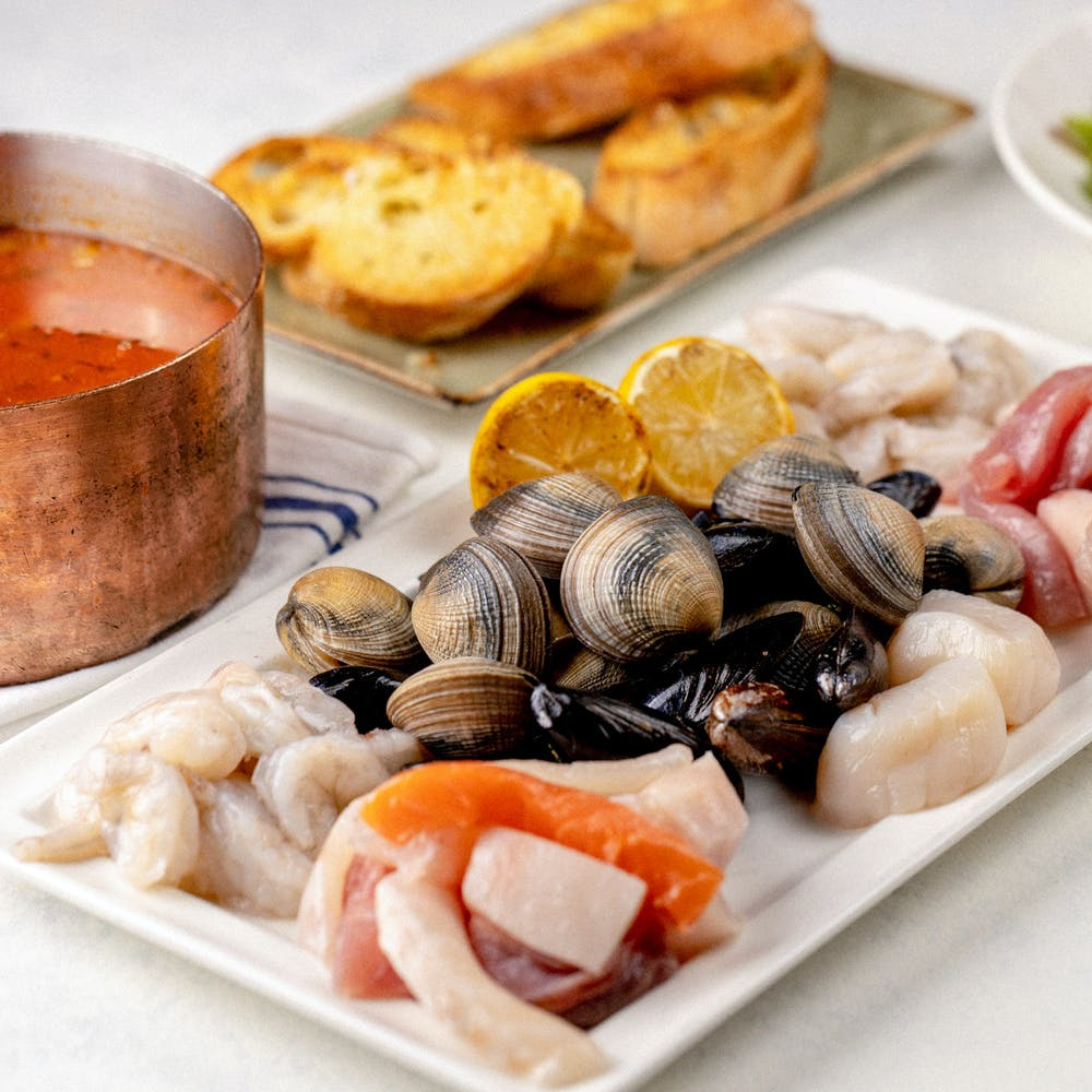 Cioppino ingredients including pot of marina and assortment of shrimp, scallops, mussels, clams, fish and crabmeat.