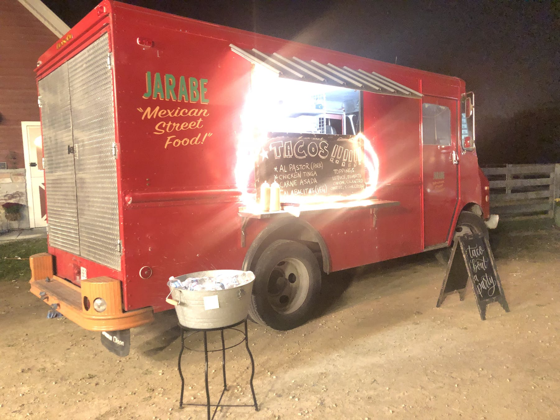 a picture of a red catering truck at night