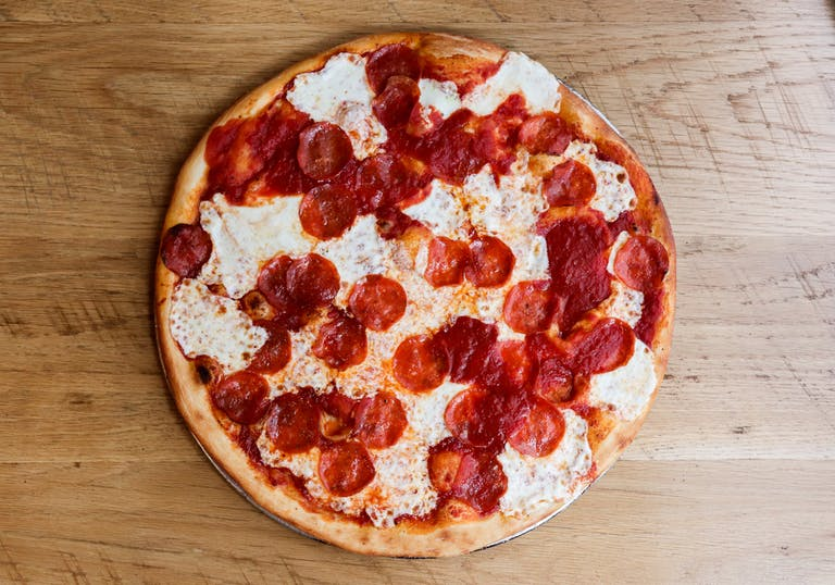 a pepperoni pizza sitting on top of a wooden cutting board