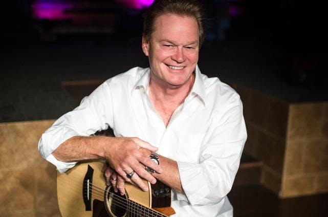 Doug Stone holding a guitar