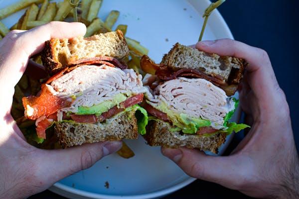 a hand holding a half eaten sandwich on a plate