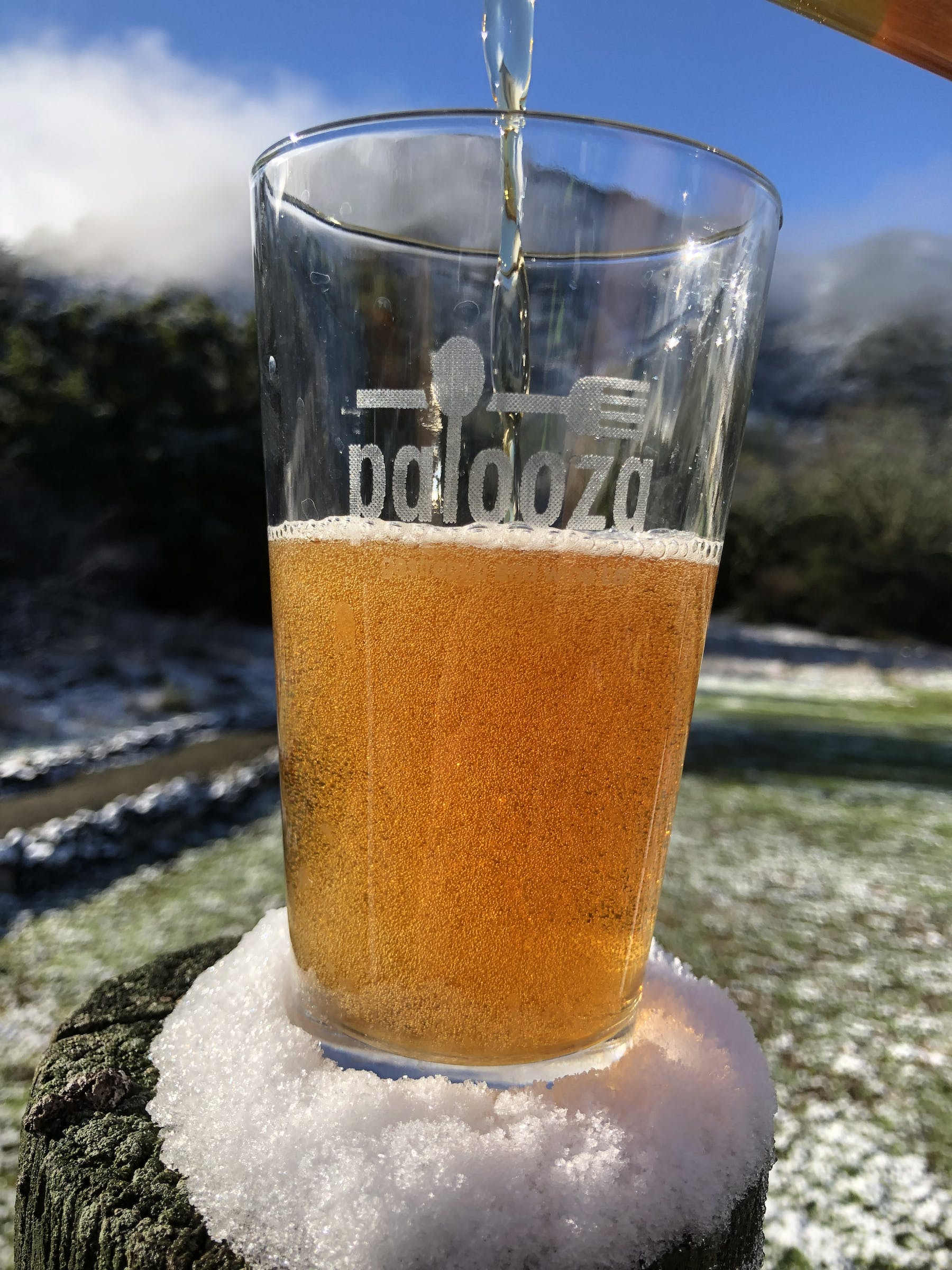 a glass of a beer sitting on a small rock