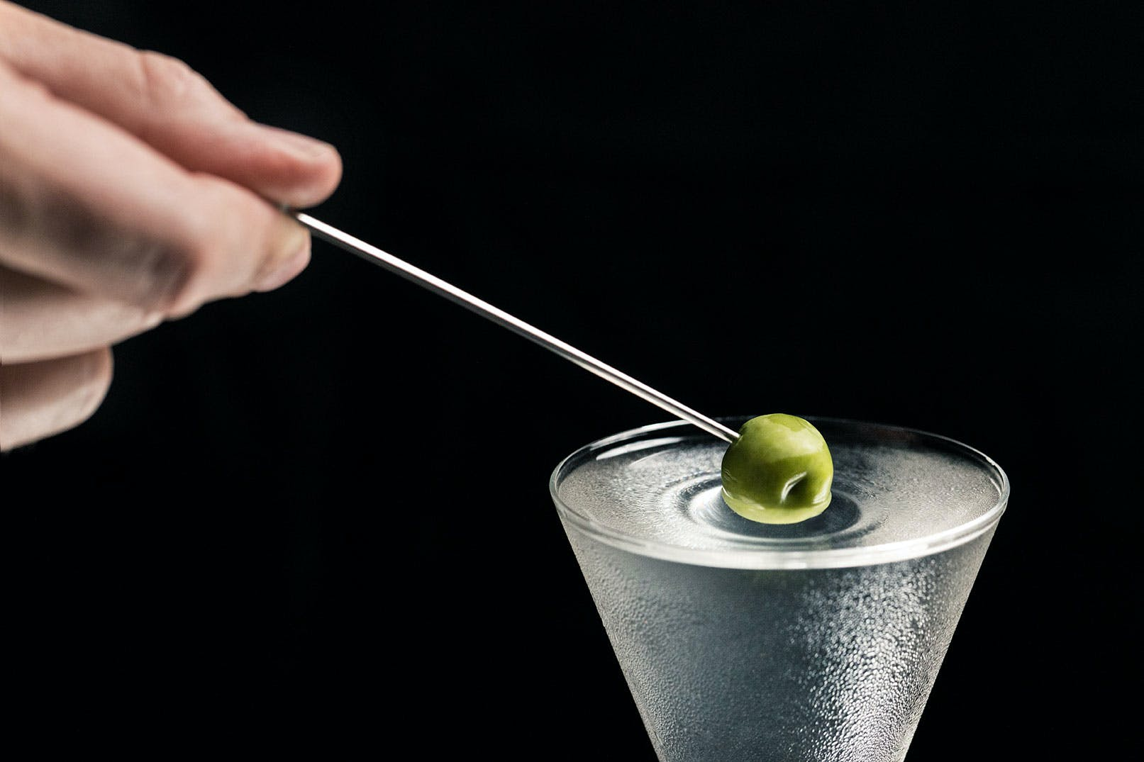 a hand holding an olive over a martini