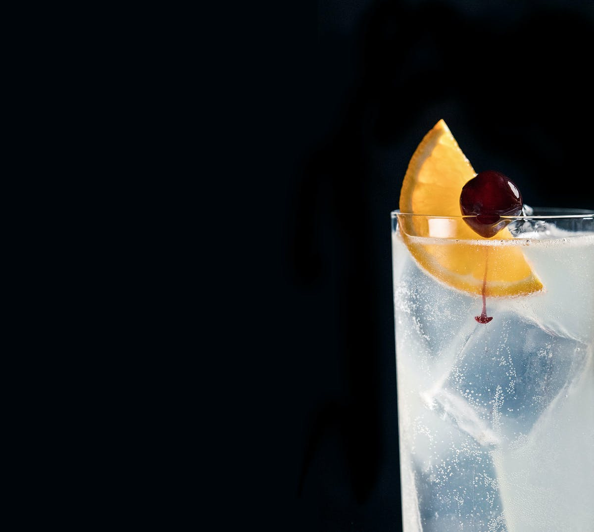 a cocktail served on a glass with an orange slice and a cherry