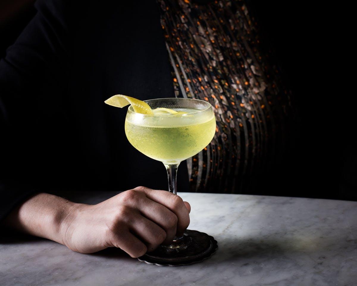 a hand holding a cocktail glass