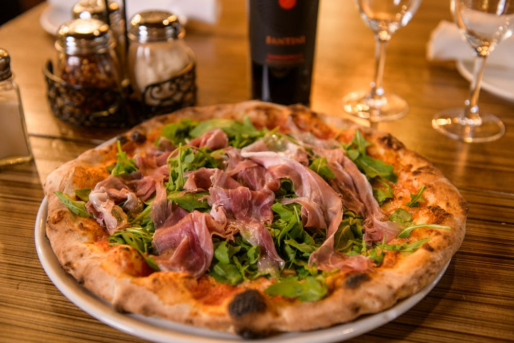 a pizza sitting on top of a wooden table topped with glasses of wine