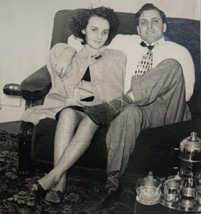 a vintage photo of a man and a woman sitting on a bench