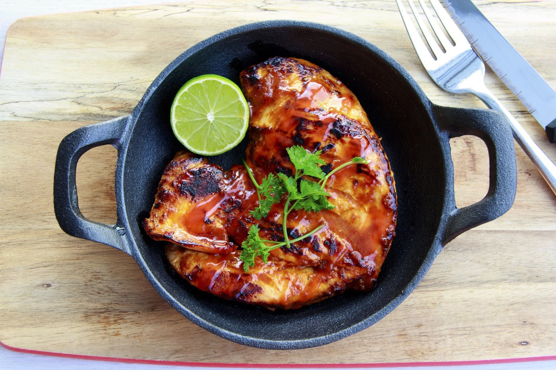 chicken on a frying pan sitting on top of a wooden table