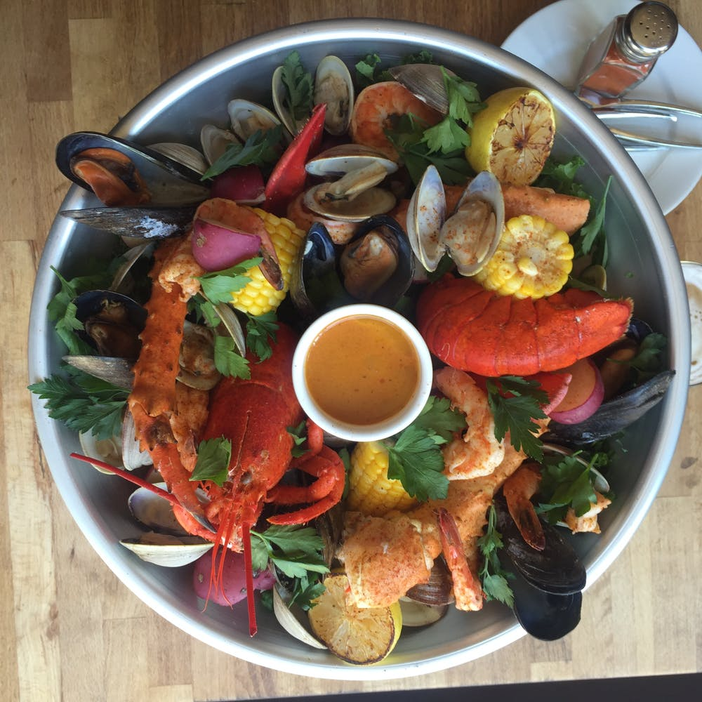 a seafood platter with shrimp, lobster, crab, clams, potatoes and corn