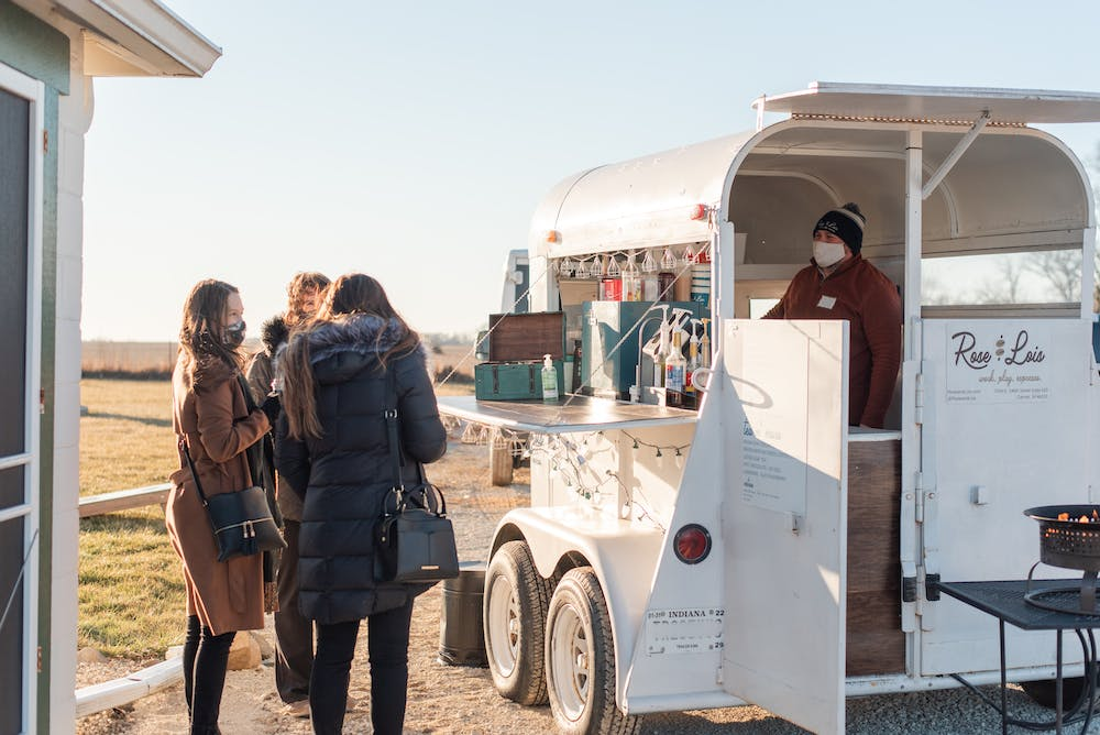 a group of people standing outside of a food truck