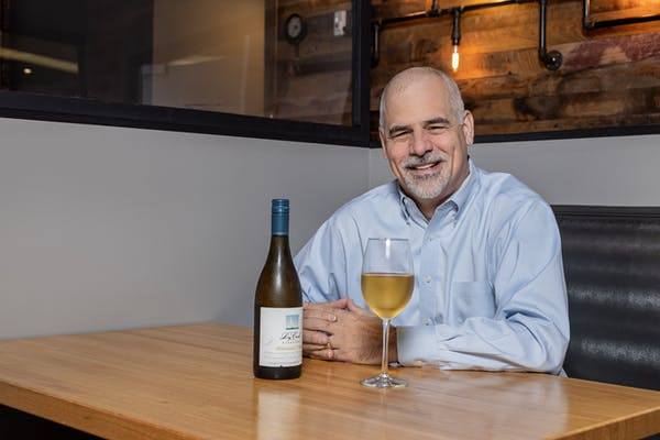 a man sitting at a table with wine glasses and smiling at the camera