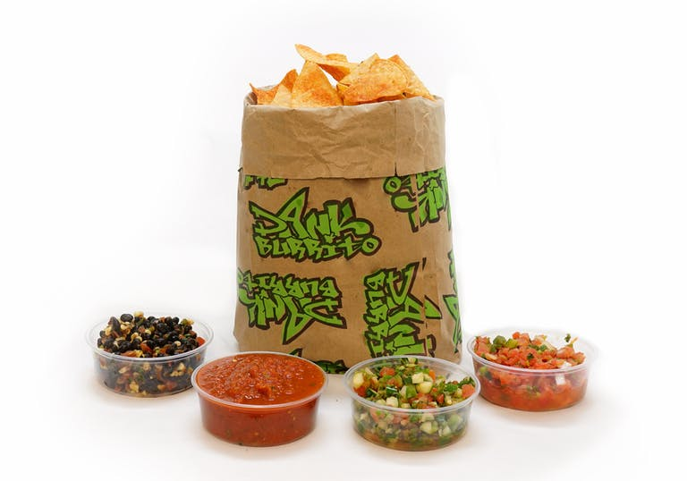 Chips on a brown paper bag and 4 different salsas