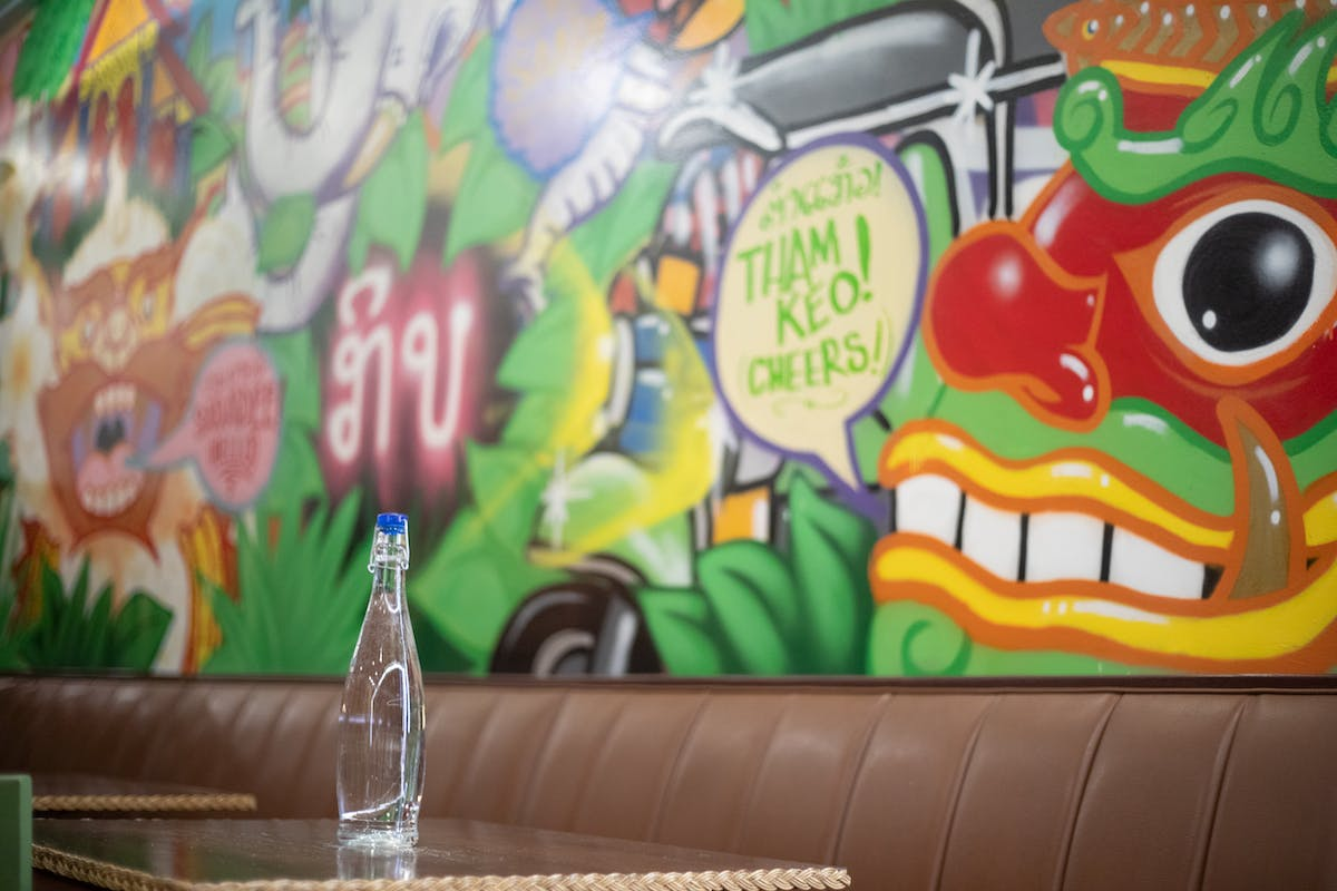 a table with a bottle of water on it in front of a mural wall