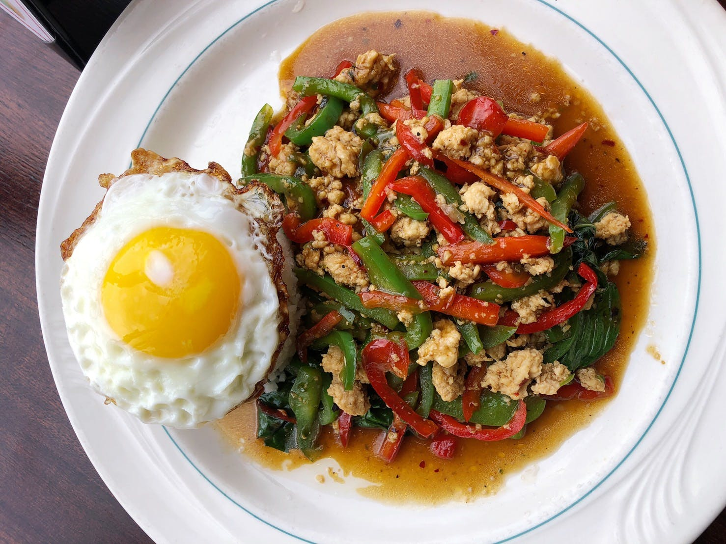 a white plate topped with meat, egg, and vegetables