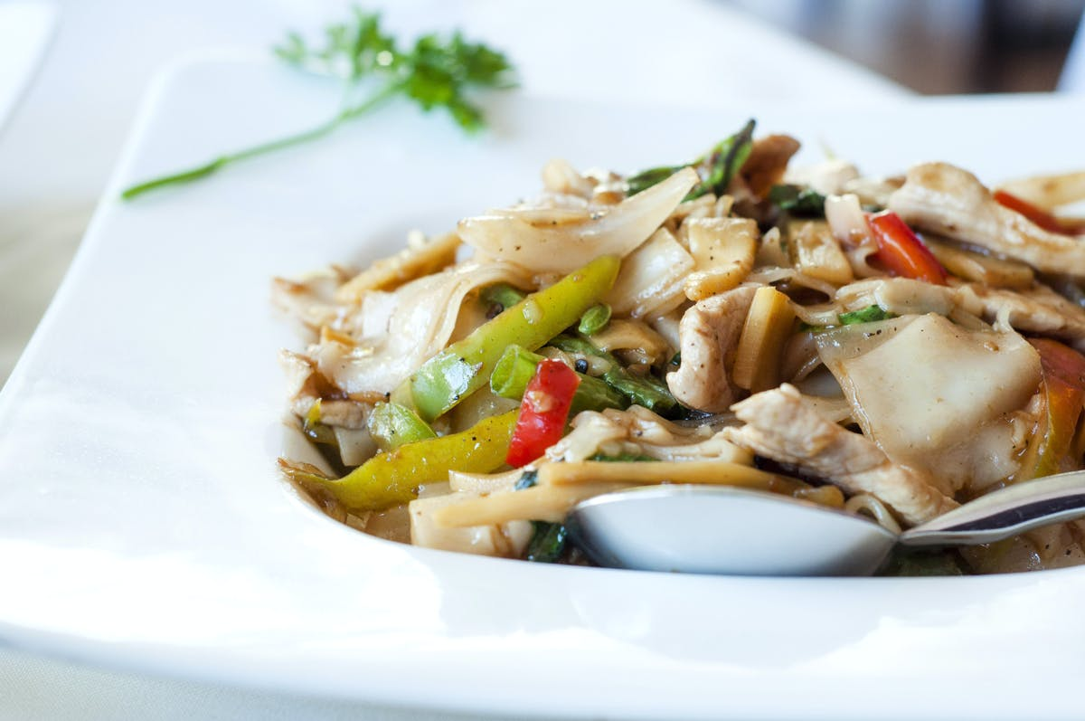 a white plate topped with shredded grilled chicken breast and vegetables