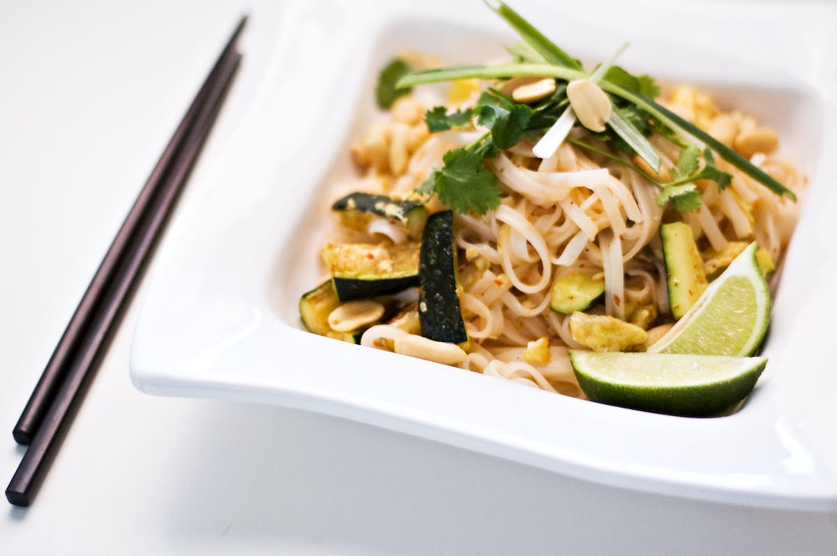 a bowl filled with thai noodles and shredded grilled chicken with vegetables