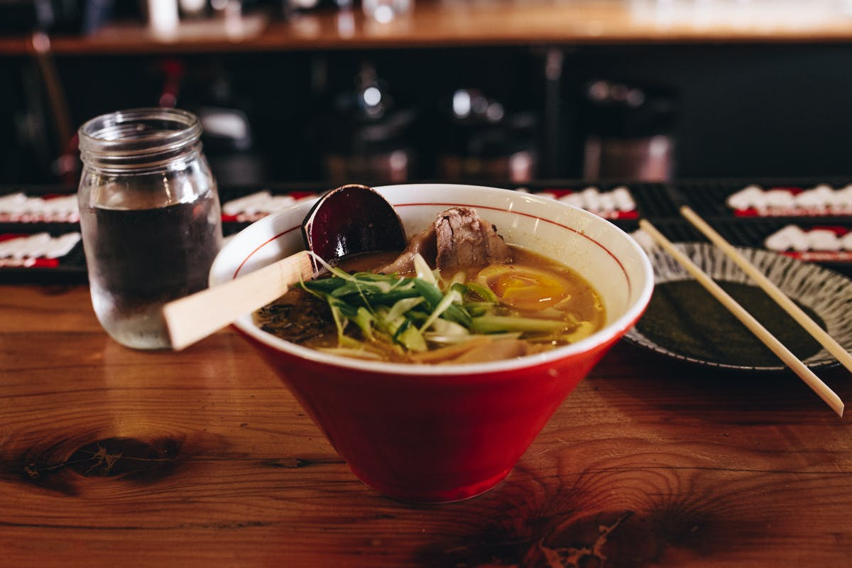 a red bowl filled with soup, thai noodles, meat and vegetables