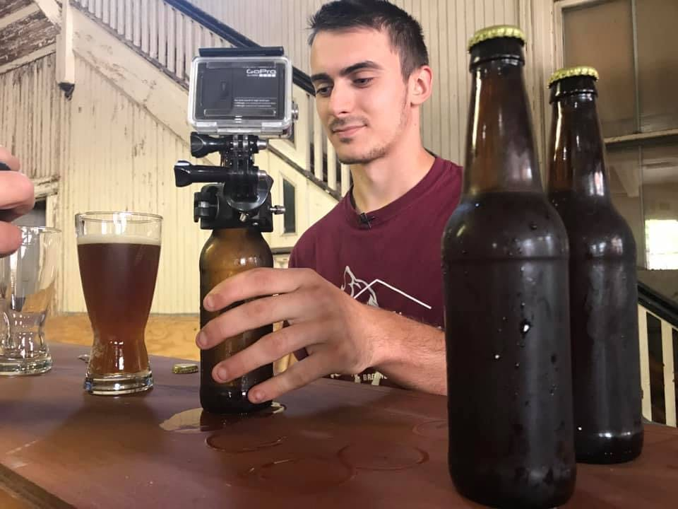 a person holding a glass of beer on a table