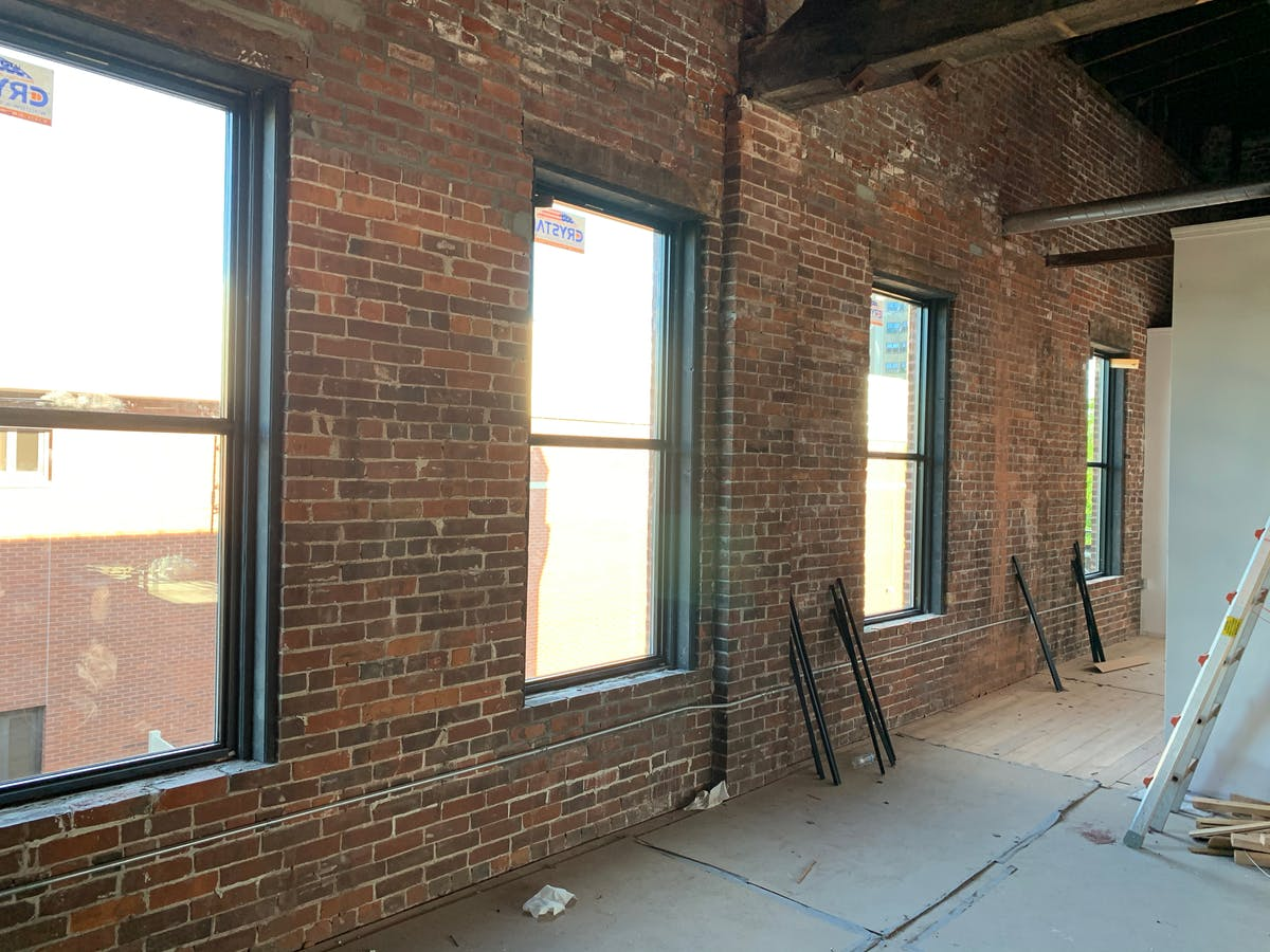 a room with brick walls and a large window