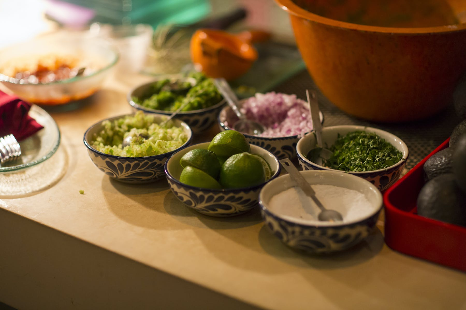 onions, lemons, sauce and cilantro in bowls on a wooden table