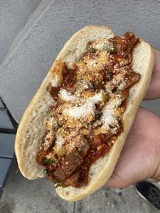 a hand holding a half eaten hot dog