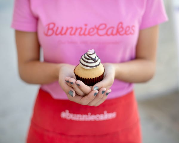 a person dressed in pink holding a cupcake with both hands